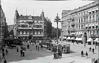 Stureplan före år 1918 med Hôtel Anglais och myllrande folkliv, spårvagnar linje 3 och 5, hästkärror, cyklande och gående människor i halmhatt.