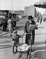Kvinna med barn och barnvagn gående på Götgatan samtidigt som hon läser tidningen Aftonbladet.