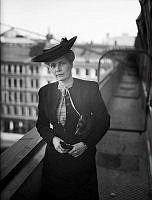 Alva Myrdal i hatt och dräkt på en terrass.