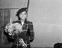 Sångerskan Josephine Baker med blommor i famnen.