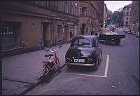 Kungstensgatan västerut mot Sveavägen vid Luntmakargatan. Bil av modellen Austin 80 och en moped parkerad utanför Kungstensgatan 31.