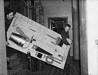 Två män bär nödvändiga verktyg och utrustning  till skyddsrum.