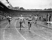Under Internationella dövstumspelen på Stadion i Stockholm korsar kvinnor mållinjen i löpning.