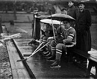 Ishockeyspelare sitter i avbytarbåset med paraplyer på Stadion under matchen mellan Hammarby - Göta.