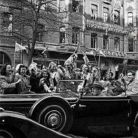 Fredsdagen den 7:e maj 1945.   Glada människor i bilar och på gatan viftar med flaggor på Birger Jarlsgatan.