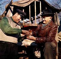 Två män tar en snus framför en båtställning.