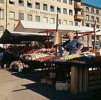 Torgstånd på Östermalmstorg med grönsaker och blommor.