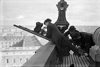 Filmarna förevigar vaktparadens på Slottets borggård i fågelperspektiv från taket på Storkyrkan. För säkerhets skull fick två medarbetare hålla fast stegen medan filmaren handvevade kameran.