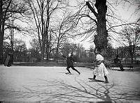 Humlegården norrut med Karlavägen i fonden. En flicka och en pojke leker i förgrunden. En man sitter på en parkbänk. En kvinna med parasoll passerar.