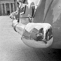 Parti av kungliga slottet samt fotografen speglade i kofångare på bil. I bakgrunden Kanslihuset.