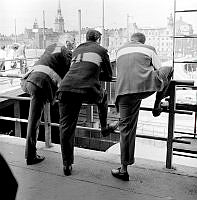 Tre män lutade mot ett räcke vid Slussen. Gamla Stan till vänster i bakgrunden, till höger Saltsjörampen.