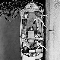 Passagerare i motorbåt med upprullat kapell väntar på slussning.