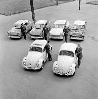 Uppställda bilar med välklädda män: fyra Opel Rekord och två Volkswagen.
