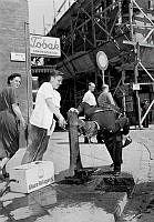 Hötorget. Högtryck över Sverige. Glassförsäljaren Rune Svensson hjälper polismannen Roland Lannerström att släcka törsten ur en vattenpump vid Konserthuset. Byggnadsställningar i hörnet av Sergelgatan