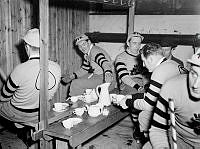 Östermalms Idrottsplats. AIK:s bandylag har fikapaus i omklädningsrummet.