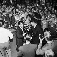 Paul Anka. Gröna Lund. Kanadensiska rock 'n' roll sångaren Paul Anka uppträder på scenen. I publiken trängs ungdomar med autografblock.