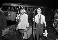 Resenärer vid långfärdsbussar dagen före julafton. Två kvinnor med bagage och vintersportutrustning.