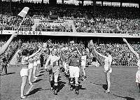 Råsundastadion. Fotbollsmatch mellan Sverige-Danmark. Spelarna på väg in på planen mellan en rad av hejarklackstjejer.