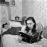 Mariane Orlando. Porträtt av balettdansösen Mariane Orlando i sitt hem, läsandes en bok i sängen. Orlando blev år 1953 premiärdansös vid Operan, med sina 19 år den yngsta dittills.