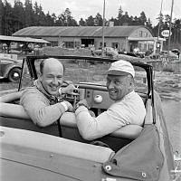 Grupporträtt av Lennart Hyland och Gunnar Olsson i en sportbil. I bakgrunden en Esso-mack.